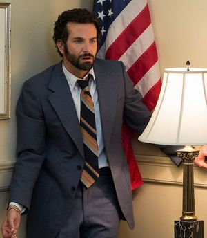 Bradley Cooper makes face, wears gold