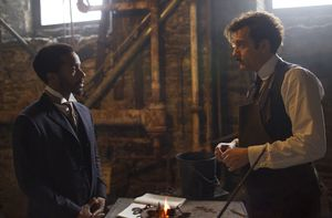 André Holland and Clive Owen working in the basement in The