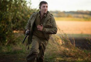 Logan Lerman running around as Norman Ellison in Fury