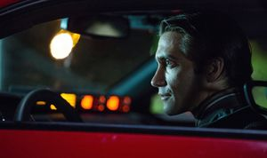 Jake Gyllenhaal watching from his cherry red Challenger in N