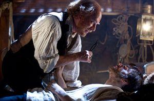 Tom Hanks as Dr. Henry Goose treating sick Jim Sturgess in C