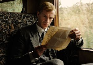 Blond James D'Arcy inspects an old document in Cloud Atlas