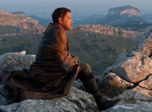 Tom Hanks looks down from a mountain in Cloud Atlas