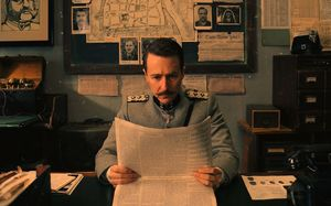 Edward Norton as Henckels reading the paper in The Grand Bud