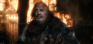 Stephen Fry as the Master of Laketown in front of burning ci
