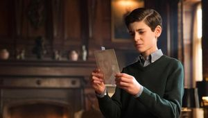 Bruce Wayne with a photo of his father