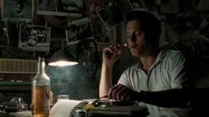Johnny Depp smokes and drinks behind his typewriter in The Rum Diary